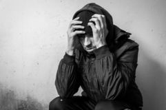 Homeless man drug and alcohol addict sitting alone and depressed on the street in winter clothes feeling anxious cold and lonely, stock images