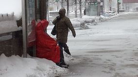Homeless man found shelter at Bus Stop during Snow Storm royalty free stock photos
