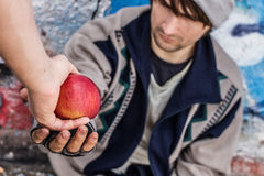 Homeless man getting food. Young homeless man being handed apple by stranger Royalty Free Stock Image