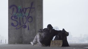 Homeless man goes to sleep at the garbage bag. Homeless man sits on concrete of abandoned building and looks on the urban city. Dirty vagabond stretches out stock footage