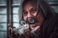 Homeless man got a lot of money on him hands that make happy face with smile - close up stock photos
