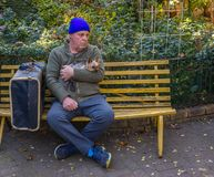 Homeless man and his dog sit on a park bench. Homeless caucasian man sit on a yellow park bench with his dog and his belongings image with copy space in Stock Photo
