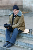 Homeless man holding his cap. Beggar and cap. Sorrowed old-aged homeless man sitting outside and holding his tip cap Royalty Free Stock Image