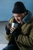 Homeless man holding his iron cup. Beggar and cup. Sad old-aged homeless man is sitting on the floor and drinking something from his iron cup Stock Photo