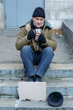 Homeless man holding his iron cup Stock Images