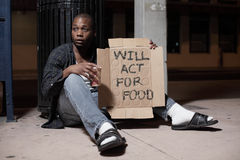 Homeless man holding a sign. Homeless actor holding a sign which reads will act for food Royalty Free Stock Image