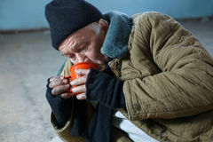 Homeless man hungrily drinking water Royalty Free Stock Photos