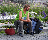 Homeless Man. Lonely old homeless man sitting on a bench on the street with his luggage Royalty Free Stock Photo