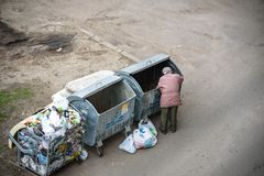 KYIV, UKRAINE MARCH 31, 2019: A homeless man looking for food in a garbage dumpster. Urban Poverty. A homeless man looking for food in a garbage dumpster. Urban royalty free stock photos