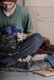 Homeless man looks a bag of clothes Stock Images