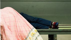 Homeless man lying at the bench. Homeless man lying at the a green bench with a blanket Stock Photos