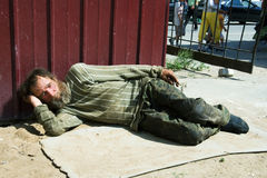 Homeless man lying on a sidewalk Royalty Free Stock Photos