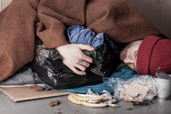 Homeless man lying on the street royalty free stock photo