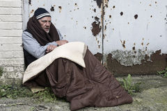 Homeless man in an old sleeping bag. Resting against a rusty door Stock Photography