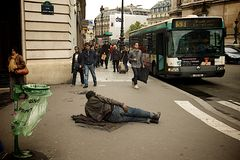 Homeless man in Paris laying on the ground. Homeless man laying on a busy street in Paris next to the Opera Garnier Royalty Free Stock Images