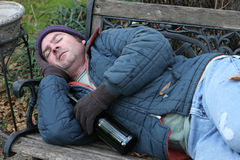 Homeless Man - On Park Bench. A homeless man asleep on a park bench with a bottle of wine stock image