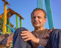 Homeless Man. Poor people in the children`s Playground at sunse Royalty Free Stock Photo