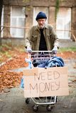 Homeless man pushing shopping cart with board need money. Royalty Free Stock Images