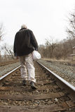 Homeless Man on Railroad Tracks. Homeless man with his posessions in a plastic bag walking along railroad tracks royalty free stock images