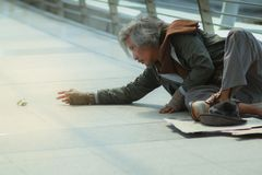 Homeless man reach hand out to money on the floor. Male Beggar, homeless man reach hand out to money on the floor stock images