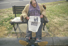 Homeless man reading newspaper on park bench, Los Angeles, California Stock Photography