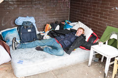 Homeless man reclining on mattress in bash. Homeless man reclining on a mattress in a makeshift bash with chairs and rucksacks wearing a black coat, training royalty free stock photography