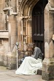 Homeless Man resting in york UK. Blanket over his knees, arm crutch leaning up against the wall. The man lokking very sad, lost and lonely. Gray hair and beard Stock Images