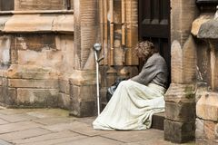 Homeless Man resting in york UK. Blanket over his knees, arm crutch leaning up against the wall. The man lokking very sad, lost and lonely. Gray hair and beard Stock Photo