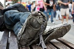 Homeless man´s rotten shoes with dirty feet on urban environment stock photography