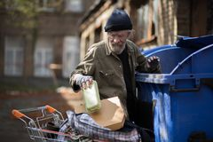 Homeless man searching for empty bottles and other stuff for recycle. Tramp trying to earn money by bringing emty bottles to recycle point Royalty Free Stock Image