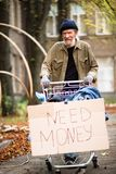 Homeless man with severe face in the street of the city. Tramp pushing shopping cart with his possessions Royalty Free Stock Photo