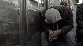 Homeless man in shabby clothes traveling by subway train. Slow motion shot of unidentified homeless man traveling by metro, he sitting with head down and face stock video footage