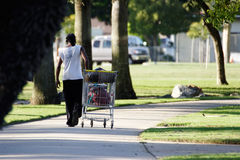 Homeless man with shopping cart stock photography