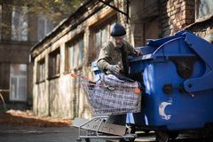 Homeless man with shopping cart collecting empty bottles for recycling. Royalty Free Stock Image