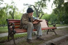Homeless man sitting on bench holding book in hands. Royalty Free Stock Photo