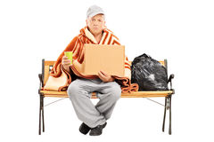 Homeless man sitting on a bench Royalty Free Stock Image