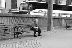 Homeless man sitting on a bench Stock Images