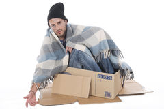 Homeless man sitting in his cardboard begging Stock Photos
