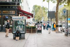 Berlin, October 2, 2017: unemployed man is sitting next to the billboard of Deutsche Bank next to people passing by. Homeless man is sitting next to the stock image