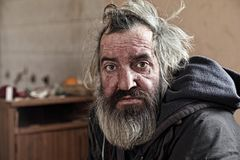 Old homeless man sitting in abandoned house. Homeless man sitting in old abandoned house Royalty Free Stock Photo