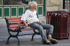 Homeless Man Sitting on a Park Bench on Stephen Avenue in Calgary Alberta. Old homeless man sleeping on a park bench on Stephen Avenue in Calgary Alberta Royalty Free Stock Image