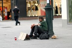 Homeless man sitting on a street with sign Royalty Free Stock Photos