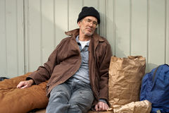 Homeless Man Sleeping. Mature homeless man sleeping in a seated posture, leaning on a metal wall, surrounded by his pack, sleeping bag, etc stock photo