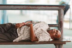 Homeless man sleeping on bench. BANGKOK, THAILAND, JULY 29, 2013 : A homeless mature man is sleeping on a bench in Bangkok, Thailand Stock Image