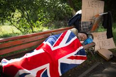 Homeless man sleeping on bench, covering with flag of Great Britain. Royalty Free Stock Images