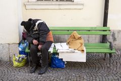 Homeless man sleeping on a bench. Homeless man in dirty clothes sleeps on a green bench in the center of Ljubljana, Slovenia stock images