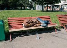Homeless man sleeping on the bench Stock Images
