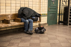 Homeless man sleeping on the bench in New York City subway station covered by own coat.  Royalty Free Stock Photos