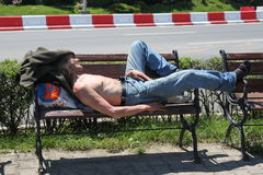 Homeless. Man sleeping on a bench parched by the sun in Sibiu,Romania Stock Photography