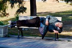 A homeless man sleeping on bench park Stock Photos